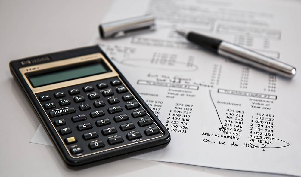 Blatt mit Zahlen und einem Füller sowie Taschenrechner zu dem Thema im Lohnsteuerhilfeverein nebenberuflich Einkommensteuerberatung