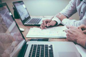 Foto mit zwei Computern und zwei Menschen, die auf einem Blatt Notizen machen in Bezug auf im Lohnsteuerhilfeverein nebenberuflich Einkommensteuerberatung