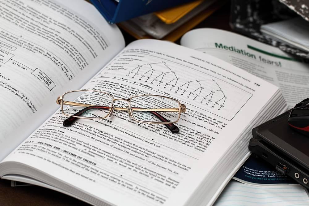 Aufgeschlagenes Buch mit Brille oben drauf im Zusammenhang mit im Lohnsteuerhilfeverein nebenberuflich Einkommensteuerberatung