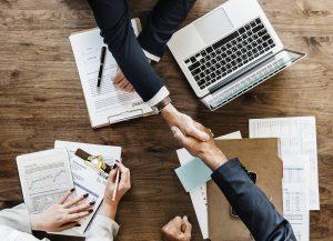 Drei Menschen an einem Tisch mit einem Computer sowie weiteren Unterlagen und zwei davon geben sich die Hand im Zusammenhang mit im Lohnsteuerhilfeverein nebenberuflich Einkommensteuerberatung