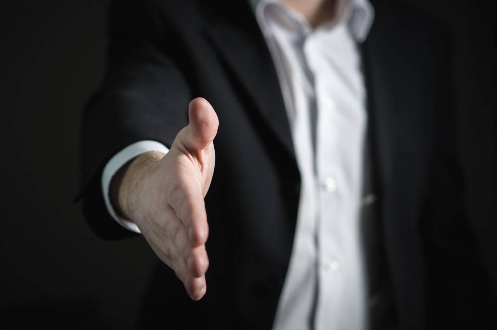 Zweigstellenleiter reicht beim Lohnsteuerhilfeverein Beratungsstelle eröffnen einem Mitglied die Hand