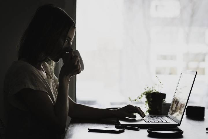 Eine Frau am Tisch bewirt sich am Laptop auf Lohnsteuerhilfeverein sucht Mitarbeiter und trinkt dabei Kaffee