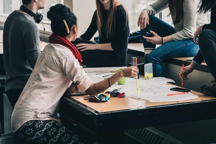 Mehrere Personen sitzen um einen Tisch, auf dem Schreibutensilien liegen