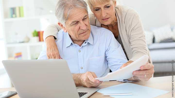 """Zwei Senioren lesen einen Steuerbescheid für Rentner. Ab jetzt mit """"Vorläufigkeitsvermerk"""""""